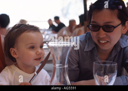 Woman and child in restaurant. - Stock Photo