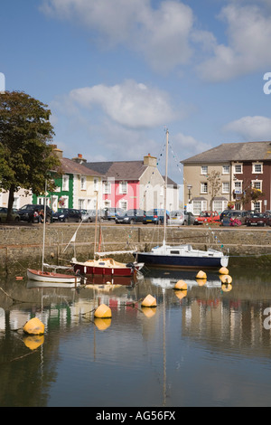Attractive colourful quayside Georgian houses reflected in calm water of harbour with moored boats Aberaeron Ceredigion