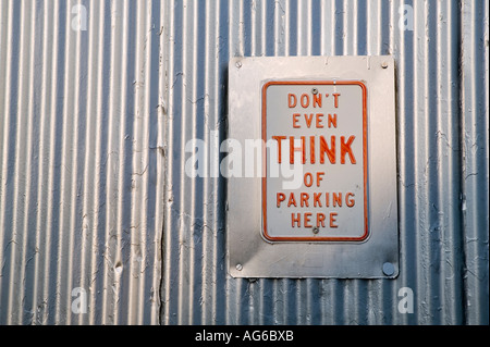 Don t even think of parking here no parking sign on a metal gate USA May 2006 - Stock Photo