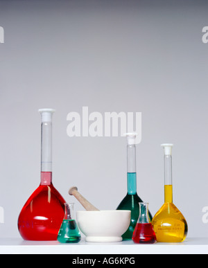 a group of flasks containing couloured liquid and a pestle and mortar - Stock Photo