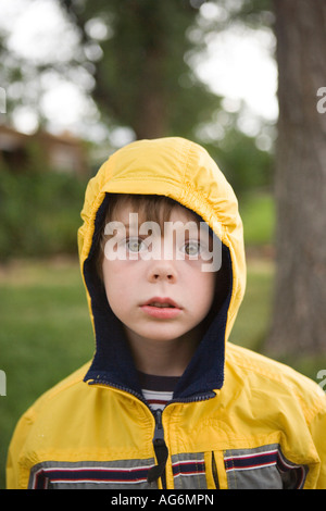five year old with serious expression outdoors, wearing yellow rain coat - Stock Photo