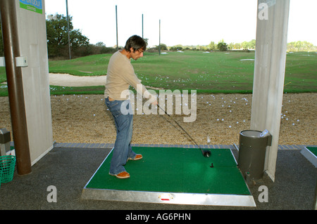 Image of a golfer on a driving range tee hitting a golf ball with a driver. Golf ball in mid air with movement. - Stock Photo