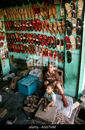 India Rajasthan Barmer people children in shoe shop - Stock Photo