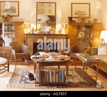 Lamps And Mirror On Mantelpiece In Living Room With Wicker Coffee Stock Photo
