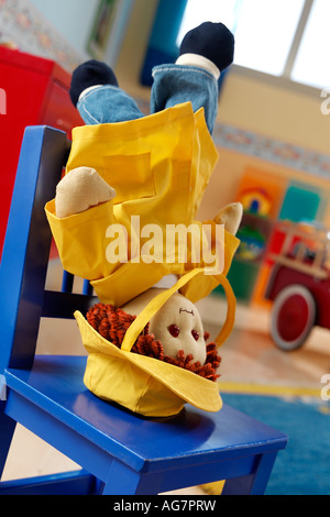 Baby doll in yellow rain coat set head down on a blue chair in kid's toy room - Stock Photo