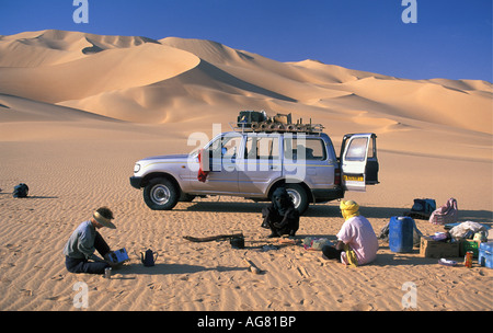 Niger Agadez Tourist and local guide relaxing on desert with 4x4 car in background - Stock Photo