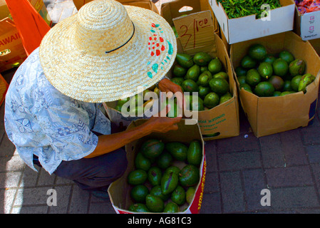 A man sells fruit and vegetables at a stand in Honolulu Hawaii at the Aloha Stadium swap meet. - Stock Photo