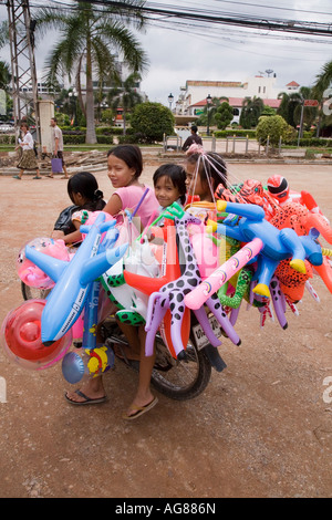 Laos family on a motorcycle in Vientiane with their Inflatable toys for sale - Stock Photo