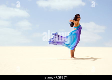 attractive dark skinned woman standing in the wind smiling. - Stock Photo