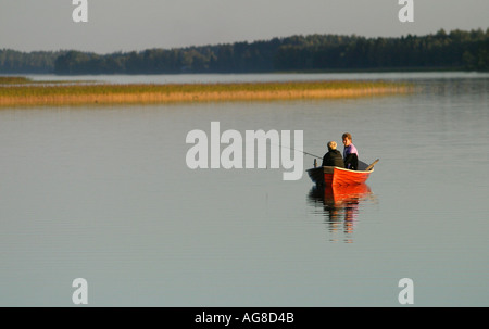 A young couple fishing from a row boat , Finland - Stock Photo