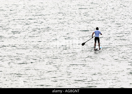 man on surfboard paddling out to sea on a calm day stand up paddle board fitness - Stock Photo
