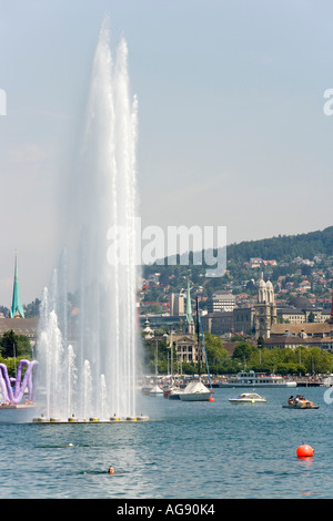 the Zurich Lake in Zurich, Switzerland. In the background the Grossmuenster Cathedral. In the foreground a fountain. - Stock Photo
