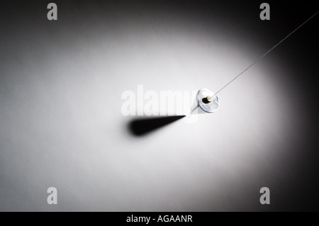 Plumb bob suspended above white surface - Stock Photo