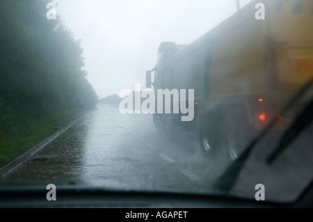 Car broken down on a dual carriageway in bad weather - Stock Photo