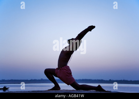 World famous yogi teacher Dr Rakesh Yogi in virbhadrasana yoga posture Ganges River India - Stock Photo