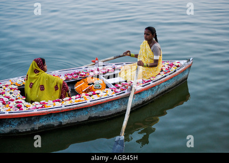 Two woman in a boat on the Ganges River selling deepak or oil lamps Ganges River  Varanasi india