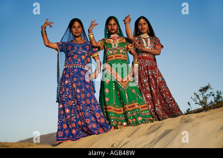 Young Indian women in a beautifully decorated saris performing a traditional Rajasthani dance Thar desert outside - Stock Photo