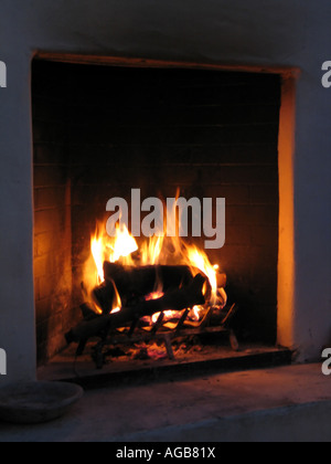 A lit fireplace in an open courtyard at night - Stock Photo