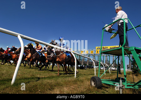 At Brighton Races the starter starts the 3 30pm race - Stock Photo