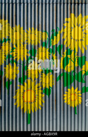 Sunflowers painted on corrugated metal barn wall, sud-Touraine, France. - Stock Photo