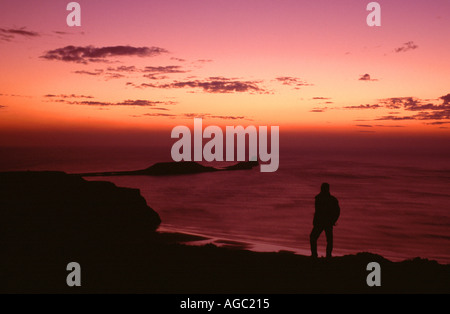 A FIGURE SILHOUETTED ON RHOSSILI DOWN WATCHING THE SUN SET OVER WORM'S HEAD, Gower Peninsula, West Glamorgan, South - Stock Photo