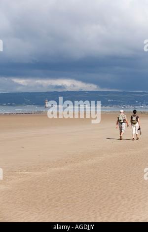 Elderley couple walking on deserted beach - Stock Photo