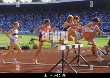 Men jumping hurdle during steeplechase race - Stock Photo