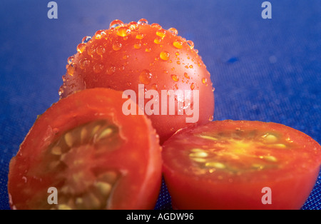 Cherry tomatoes on blue chopping board - Stock Photo