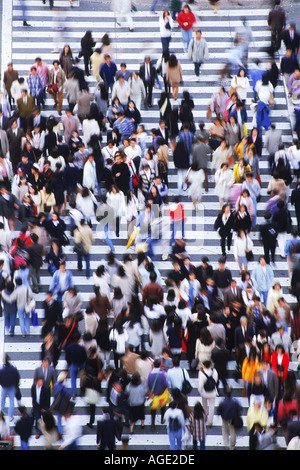 Pedestrians filling crosswalks in Shibuya district of Tokyo - Stock Photo