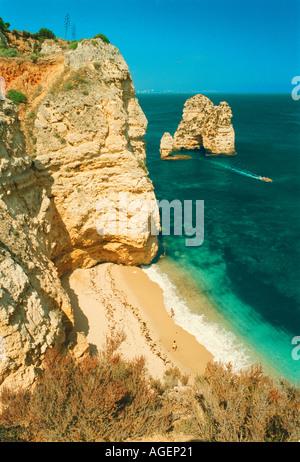 Two people enjoying a swim at the secluded PRAIA DONA ANA beach at Ponta da Piedade close to Lagos on the Algarve - Stock Photo