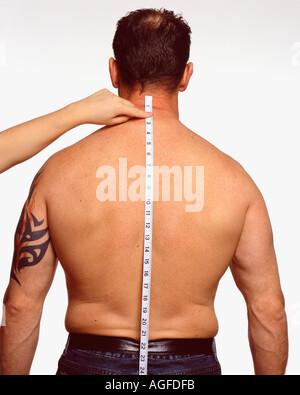 Measuring along male back - Stock Photo