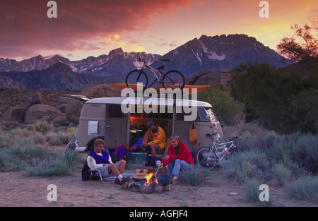 Two men and a woman sitting around a campfire next to a van with mountain bikes and a kayak and mountains in the background