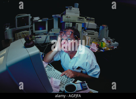 A frazzled worker looks up from his computer monitor at two donuts sitting on top of the monitor - Stock Photo
