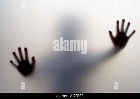 The hands of a child pressed up against the frosted glass of a door - Stock Photo