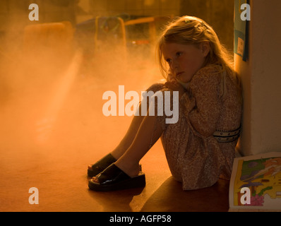 Little girl in burning school - Stock Photo