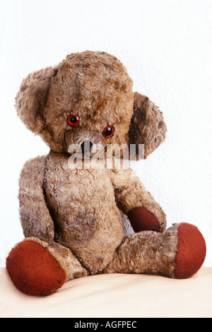 Well loved scruffy old teddy bear seated - Stock Photo