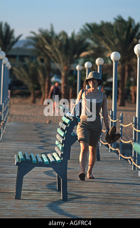 Woman walking towards an empty seat on a jetty Red Sea coast at Nuweiba Sinai Egypt Vacation photograph Middle East - Stock Photo