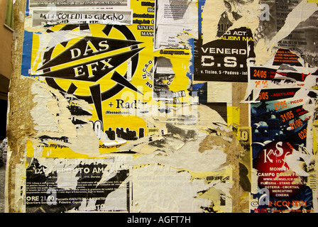 Street Art: Student protest posters interspersed with dance clubs Padua Italy - Stock Photo
