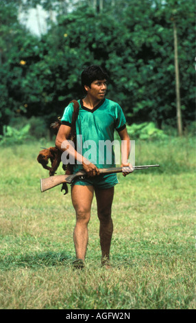 Bolivia Reyes Young man walking with gun and dead Howler monkey - Stock Photo