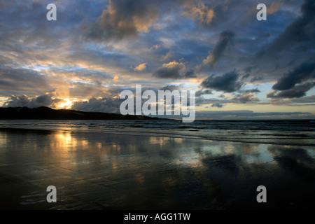 Sunset over sand dunes at Ahipara Ninety Mile Beach New Zealand - Stock Photo