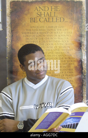 Male Black Student at work studying from text book in front of religious poster - Stock Photo