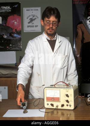 laboratory technician measuring radioactivity of a rock sample with a geiger counter - Stock Photo