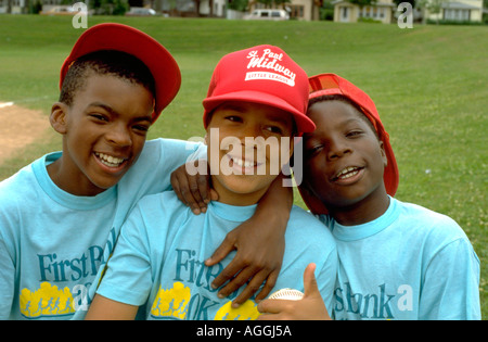Black happy inner city ball player friends age 10 with arms around each other. St Paul Minnesota USA - Stock Photo