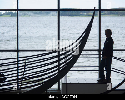 Tourist looking at the remains of a Viking ship in the Viking Ship Museum Roskilde North Zealand Denmark - Stock Photo