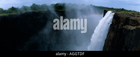 Africa Zambia Mosi Oa Tunya National Park Rainbow forms as Zambezi River pours over Main Falls of Victoria Falls - Stock Photo