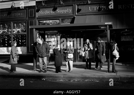 street scene in black white New York City people waiting for a bus in a bus stop - Stock Photo