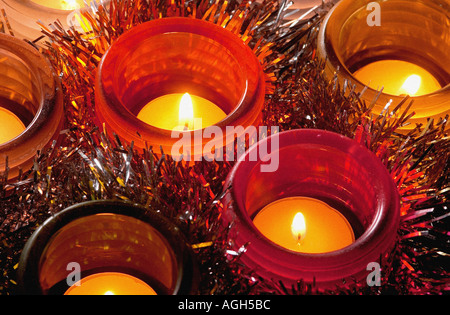 several tea lights burning in coloured glass holders at Christmas with tinsel between them - Stock Photo