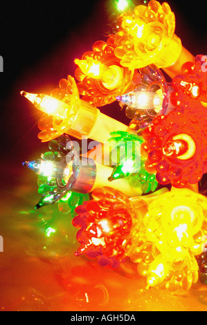 Bundle of coloured Christmas tree lights illuminated on white ...