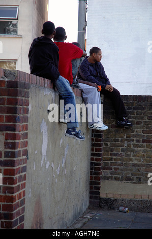 Young lads out of school bored and fed up sitting on wall in Brixton South London waiting. - Stock Photo