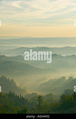 Misty view across the hills of Tuscany below a blue sky. Taken from San Gimignano, Tuscany, Italy at sunrise - Stock Photo